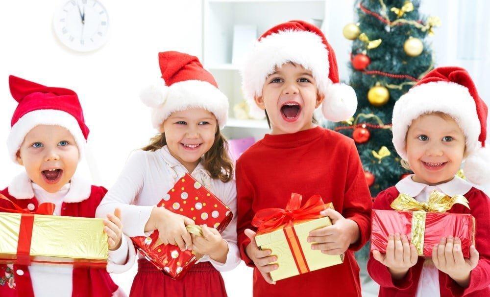 Børn i forskellige aldre med julegaver i hænderne